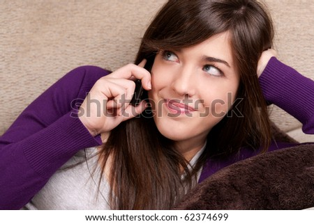 Young female talking by telephone smiling lying on couch close-up - stock photo