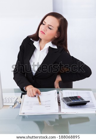 Young female tax consultant suffering from backache sitting at desk in office - stock photo
