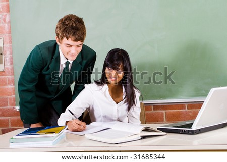 young female teacher and high school student in classroom - stock photo