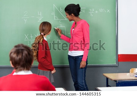 Young female teacher teaching mathematics to students on board in classroom