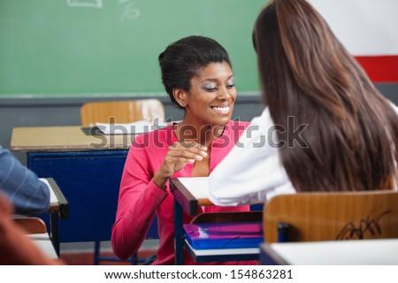 Young female teacher teaching teenage schoolgirl at desk in classroom - stock photo