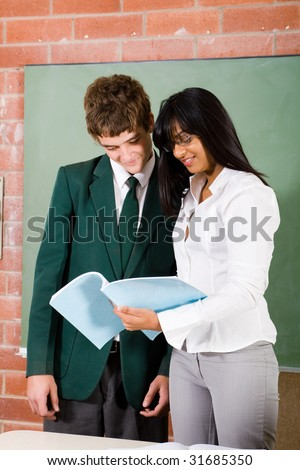 young female teacher with high school student - stock photo