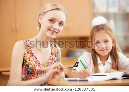 Young female teacher working with children at school - stock photo