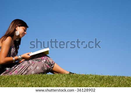 young female teenager at the park reading a book - stock photo