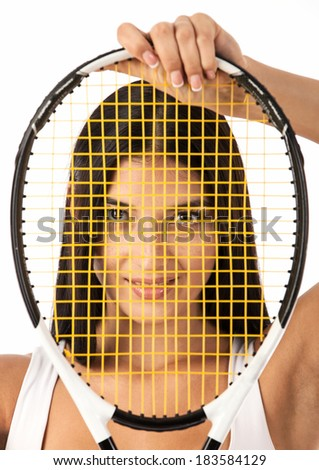 Young female tennis player looking through strings of racket over white  - stock photo