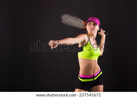 Young female tennis player posing with racket on black background - stock photo