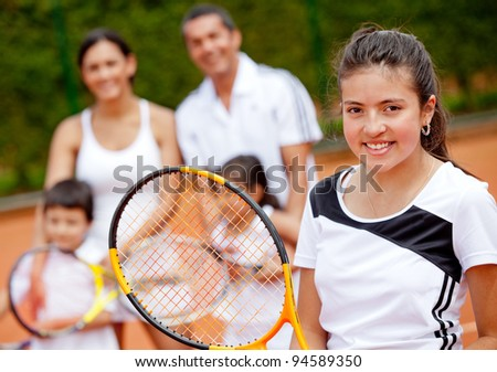 Young female tennis player with her family at the background - stock photo