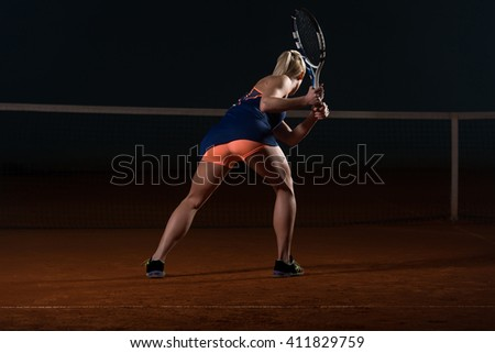 Young Female Tennis Player With Racket Ready To Hit A Tennis Ball - Back View - stock photo