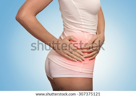Young female touching her right side in pain colored in red. Kidney inflammation and therapy. Medicine and health care concept. Blue background  - stock photo