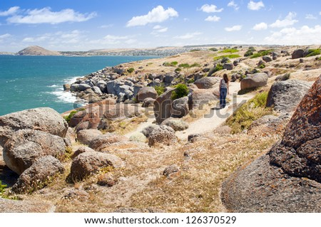 Young female tourist along the edge of Granite Island, South Australia, near Victor Harbour. - stock photo