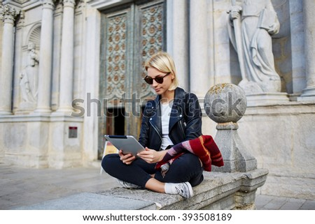 Young female tourist in sunglasses is searching way in navigation on touch pad, while resting after tour in old church. Woman is enjoying good movie on digital tablet during her free time in weekend - stock photo