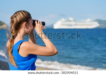 Young female tourist looking through binoculars at white cruise ship (liner) and enjoying scenic sea view. Woman wearing blue dress. Her hair braided in French plait. Outdoor portrait in summer. - stock photo