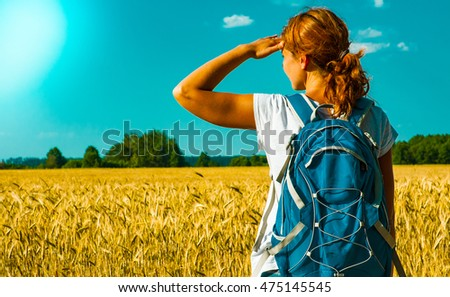 young female tourist with backpack looking into the distance near a wheat field under the hot summer sky. back view