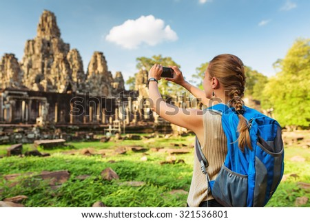 Young female tourist with blue backpack and smartphone taking picture of ancient Bayon temple in Angkor Thom on blue sky background. Siem Reap, Cambodia. - stock photo