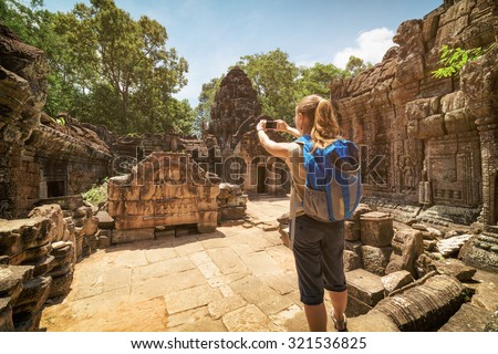 Young female tourist with blue backpack ands smartphone taking picture of the unique bas-relief among mysterious ruins of the ancient Preah Khan temple in Angkor. Siem Reap, Cambodia. - stock photo