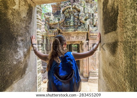 Young female tourist with blue backpack coming to ancient Preah Khan temple in Angkor and looking at the bas-reliefs on the walls and on mysterious ruins. Siem Reap, Cambodia. - stock photo