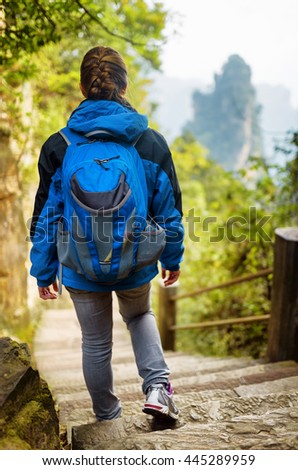 Young female tourist with blue backpack descending stairs among green foliage and enjoying beautiful mountain view, the Zhangjiajie National Forest Park, Hunan Province, China.