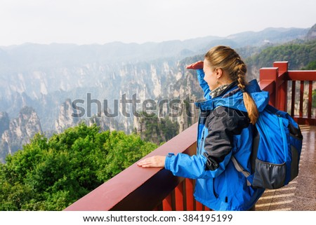 Young female tourist with blue backpack enjoying beautiful mountain view in the Zhangjiajie National Forest Park, Hunan Province, China. Her hair braided in French plait. Outdoor portrait. - stock photo