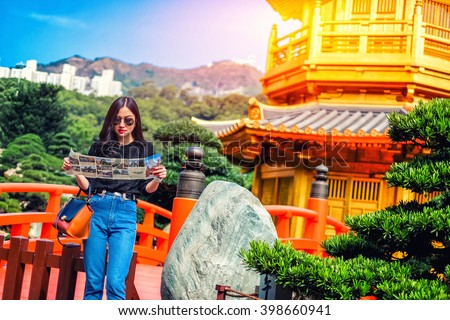 Young female tourist with map looking for a way to Gold Chinese pavilion Temple at the park in Hong Kong - stock photo
