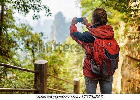 Young female tourist with red backpack among green foliage taking photo of beautiful mountain view in the Zhangjiajie National Forest Park, Hunan Province, China. Her hair braided in French plait. - stock photo