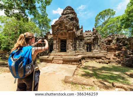 Young female tourist with smartphone taking picture of the gopura under blue sky near the entrance to ancient Preah Khan temple in Angkor. Siem Reap, Cambodia. - stock photo