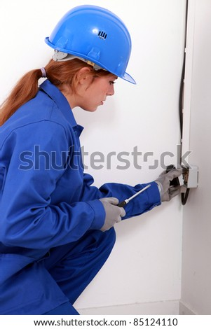 Young female trades apprentice wiring a power point - stock photo