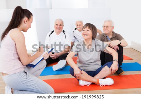 Young female trainer taking notes from senior customers at gym - stock photo
