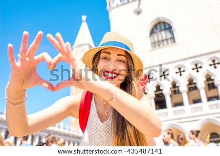 Young female traveler making heart shape with hands on San Marco square in Venice. Venice is one of the favorite tourist city - stock photo