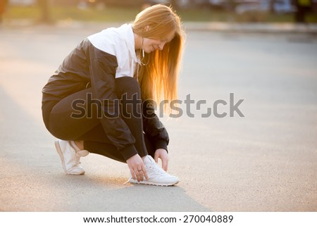 Young female tying laces on white sneakers on the street, jogger preparing for running workout. Healthy, active lifestyle concepts, copy space - stock photo