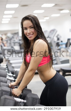 Young female using gym fitness equipment - stock photo