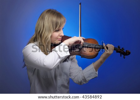 Young female violinist playing on the violin with blue background - stock photo