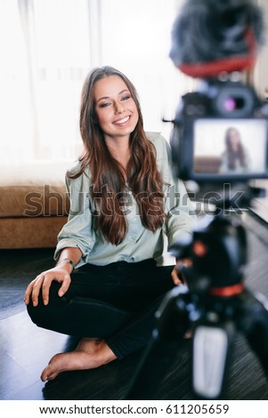 Young female vlogger on camera screen. Smiling woman sitting on floor recording her content.