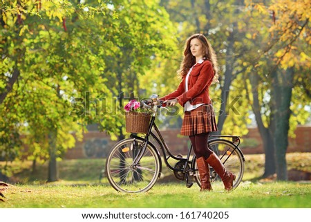 Young female walking with bicycle in a park - stock photo