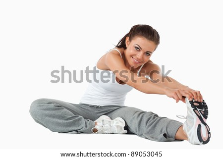 Young female warming up before workout against a white background - stock photo