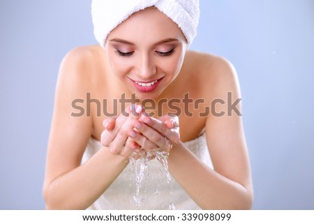 Young female washing her face with clear water - stock photo