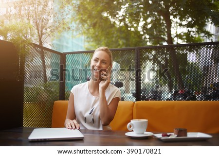 Young female with beautiful smile is talking on her mobile phone while she is relaxing in coffee shop in the fresh air,business woman is having pleasure cell telephone conversation during rest in cafe - stock photo