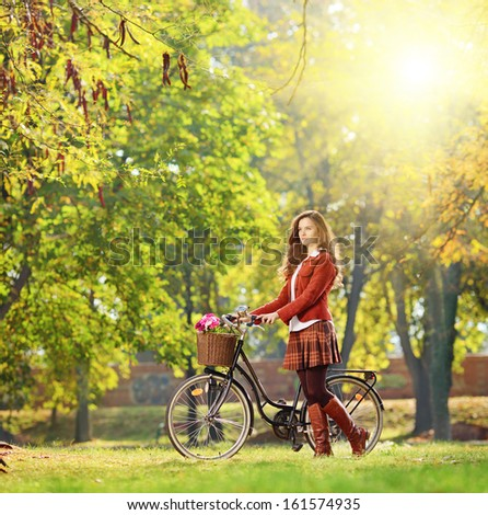 Young female with bicycle relaxing in a park on a sunny day, shot with a tilt and shift lens - stock photo