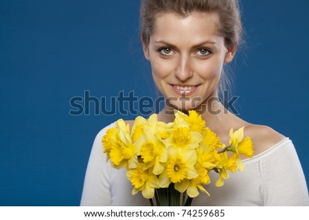 Young female with bunch of flowers on blue background - stock photo