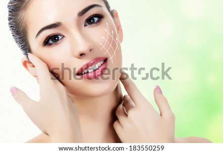 Young female with clean fresh skin, green background - stock photo
