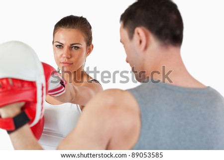Young female with her martial arts trainer against a white background - stock photo