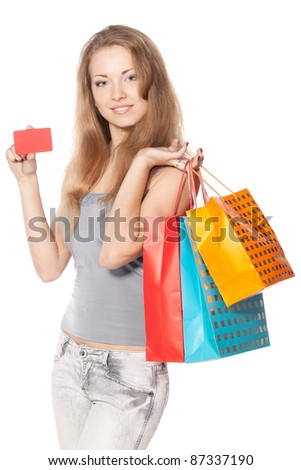 Young female with shopping bags holding blank credit card isolated on white background - stock photo