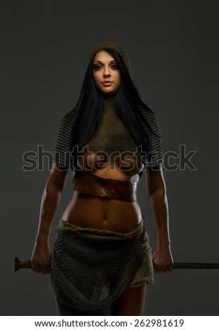Young female with sword in ancient armor on grey background - stock photo