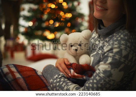 Young female with teddy bear having rest at home - stock photo