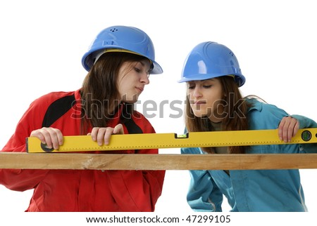 young female workers with protection helmets and overalls on white background - stock photo