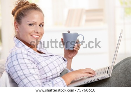 Young female working at home in bed, using laptop, drinking tea, coffee. - stock photo