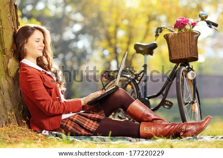 Young female working on a laptop seated on a green grass in park on a sunny day - stock photo