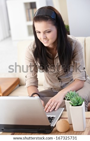 Young female working with computer at home.