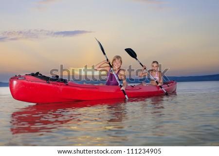 Young females kayaking on Lake Balaton at sunset - stock photo