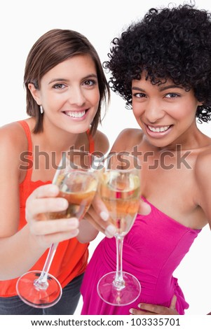 Young females smiling and clinking glasses of white wine - stock photo