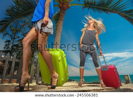 Young females  with a suitcases on the beach - stock photo